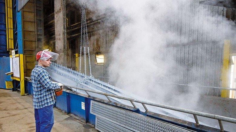 Es dampft: Am Arbeitsplatz von Marcin Bysiec kühlen Stahlteile nach dem Verzinken ab. Die Kreuztaler Firma hat den größten Verzinkungskessel Deutschlands. Er fasst 760 Tonnen flüssiges Zink.