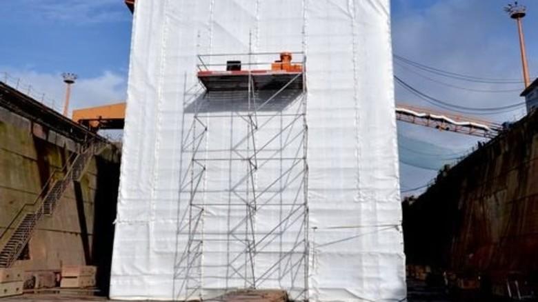 Schutz: Hinter Planen versteckt arbeitet der Sandstrahler. Foto: dpa