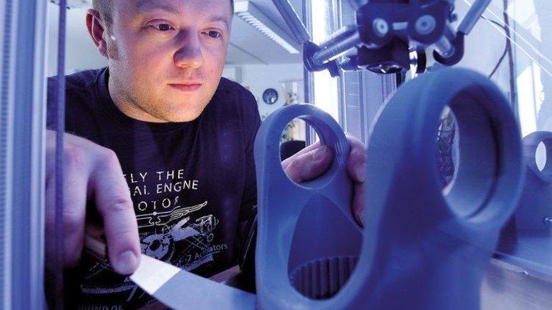 Entwicklung: Andrej Stoll holt ein Gelenkteil aus dem 3-D-Drucker im Konstruktionsbüro. Foto: Augustin