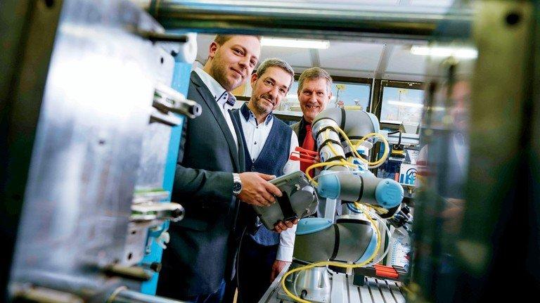 Bestaunen den neuen Roboter: Die Absolventen David Bertsch und Artur Wagner sowie der frühere Abteilungsleiter Achim Wamser (von links).