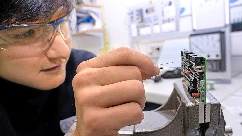 Feinarbeit: Geschickt setzt Azubi Fabian Becker elektronische Bauteile in eine Leiterplatte ein.