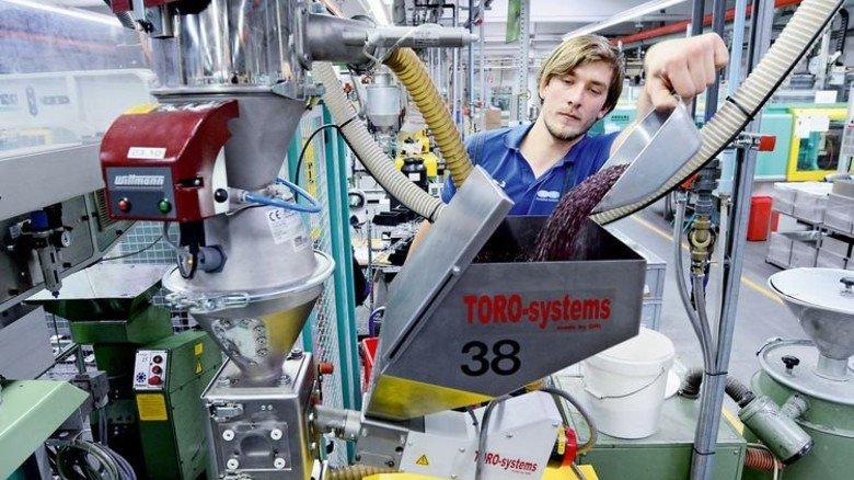In der Produktion: Patrick Beetz füllt Granulat am Spritzgießautomaten nach. Foto: Sturm