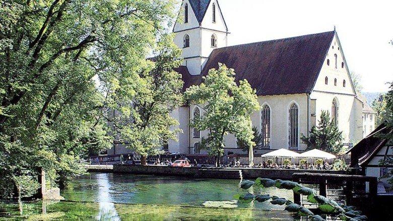 Malerisch: Das ehemalige Kloster spiegelt sich im Blautopf. Foto: Stadt Blaubeuren, Universität Tübingen, Landratsämter Alb-Donau und Heidenheim