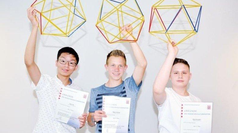 Die Sieger des Hessischen Mathematik-Wettbewerbs: Leon Xu, Robin Kistner und Nick Korjakin (von links) zeigen ihre Trophäe, ein dreidimensionales Ikosaeder-Modell. Foto: Scheffler