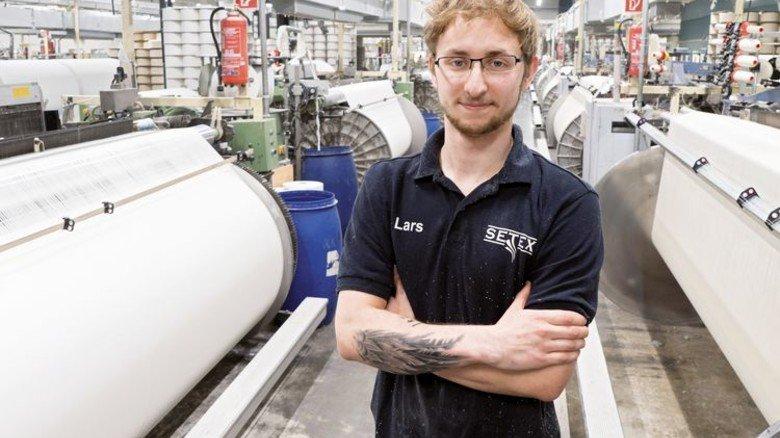 Im Betrieb: Der junge Mechaniker kümmert sich um Webmaschinen. Foto: Egbert