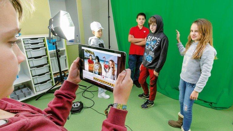 Offene Werkstätte: Sechstklässler drehen vor dem Greenscreen ein Video.