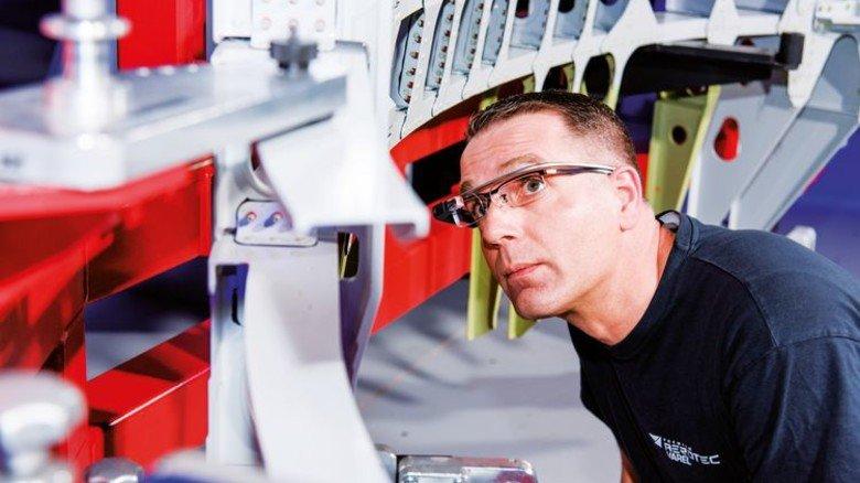 """Smarte Sehhilfe: Fluggerätmechaniker Jörg Schneider überprüft die fertigen Türrahmen vor der Auslieferung mithilfe von """"AeroGlasses"""". Foto: Premium Aerotec"""
