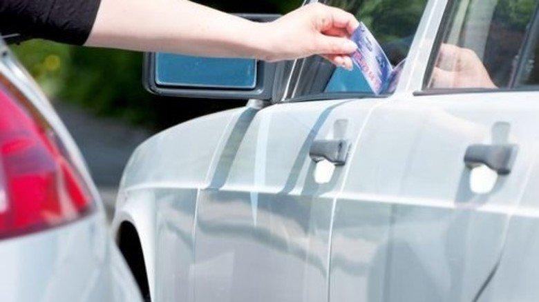 Schnelle Nummer: Auch aus dem fahrenden Auto heraus kann man Kärtchen verteilen. Foto: Roth