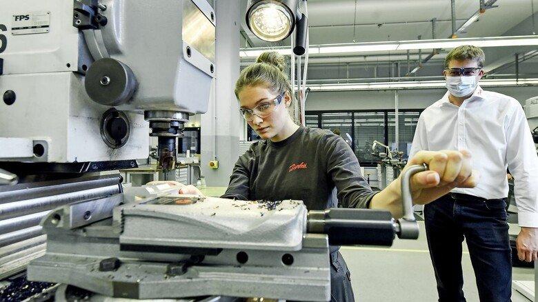 In der Lehr-Werkstatt: Ausbilder Jan Widderich mit einer jungen Auszubildenden, die gerade ein Werkstück einspannt.