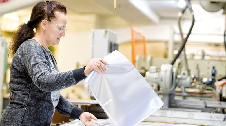 Produktion: Mitarbeiterin Anka Mikic löst bei kleineren Auflagen die Hüllen von Hand aus der Folienbahn.