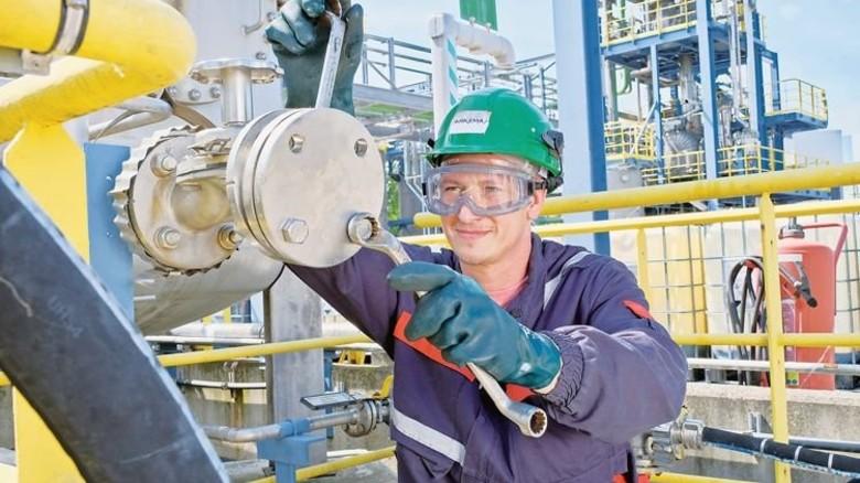 Muskelkraft gefordert: Chemikant Tobias Möhrling schraubt einen Deckel auf die Anschlussstelle eines Schlauchs. Foto: Deutsch