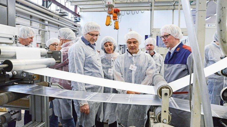 Am laufenden Band: Torben Vogt (rechts) zeigt den Besuchern der Firma Löseke eine Anlage, auf der Blockbodenbeutel produziert werden.