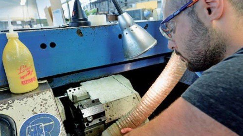 …und Altan Hacat produziert Distanzbuchsen: Mit dem Absaugrohr sichert er die diffizile Abfuhr der Späne. Foto: Bahlo