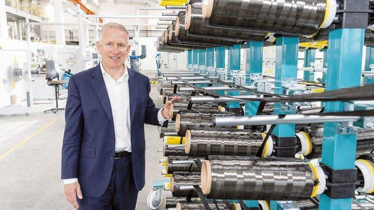 Schwarzes Material: Andreas Wüllner von SGL Carbon vor Faserbündeln, die später  in einem weiteren innovativen Verfahren, der Pultrusion, verarbeitet werden.