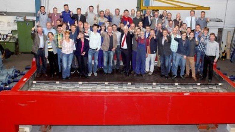 Kraftprotz mit Rekordmaßen: Die Belegschaft von Claudius Peters präsentiert gemeinsam mit Geschäftsführer Reiner Frühling in der Werkhalle den größten Walzenbrecher der Welt. Foto: Werk