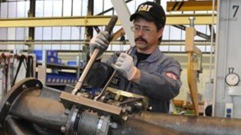 Riesen-Auspuff: Motorenschlosser Volker Gneckkow justiert Elemente an einer Abgas-Anlage, die später an einen Schiffsmotor montiert wird. Foto: Heeger
