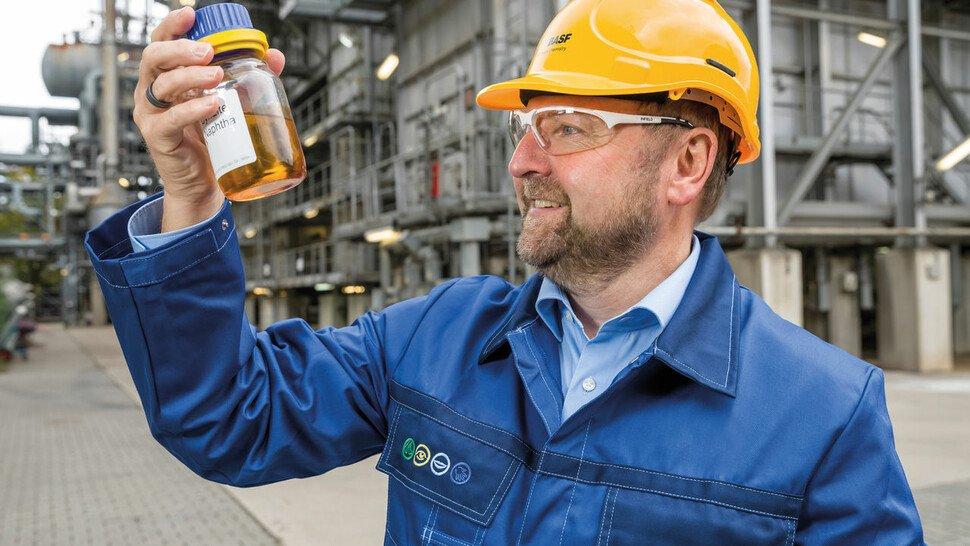 Pyrolyseöl aus Kunststoffabfällen: Ein Mitarbeiter der BASF mit einer Probe vor dem Steamcracker.
