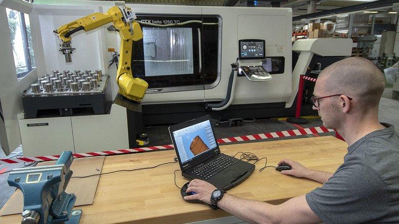Der neue Fräs- und Drehautomat: Dominik Nolden programmiert ihn gerade. Der Clou ist der gelbe Bedien-Roboter.