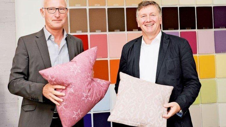 Neuheit: Geschäftsführer Johannes Dowe (links) und Josef Kölker mit Kissen aus Jacquard-Flanell. Foto: Wirtz