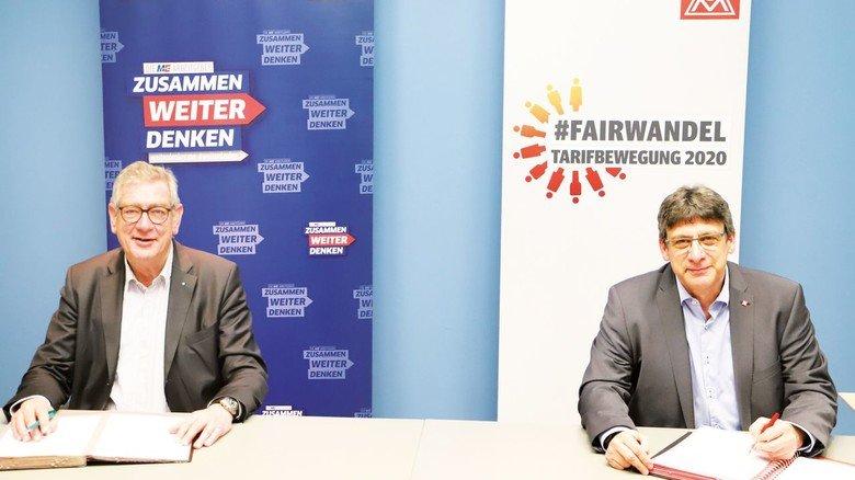 Aus Sicherheitsgründen weit auseinander: Die Verhandlungsführer in NRW, Arndt G. Kirchhoff (links) und Knut Giesler, signieren den Tarifvertrag. Der übliche Handschlag musste entfallen.