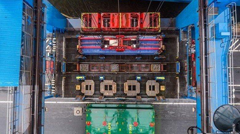 Blick aus der Fahrerkabine: Der rote Ausleger, die sogenannte Katze, greift nach einem Container. Foto: Roth