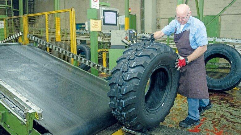 Das erfordert Muskeln: Hermann Kön legt einen Reifen für ein Baufahrzeug aufs Förderband.