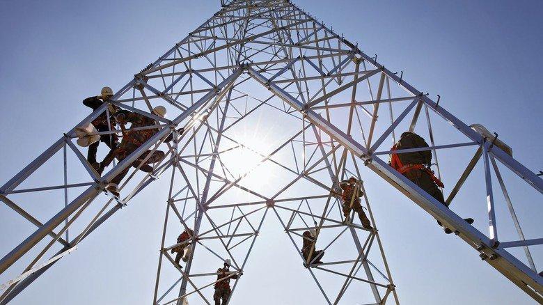 Arbeiter auf einem Strommast: Am europäischen Energie-Binnenmarkt wird jetzt kräftig geschraubt.