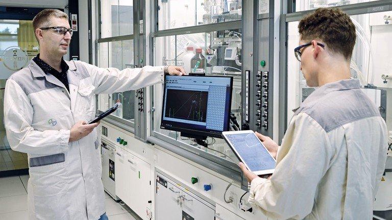 Tablets sind längst festes Zubehör im Bayer-Labor: Peter-Xaver Voits (links) erklärt einem Azubi den Datentransfer in Richtung Anlagensteuerung.