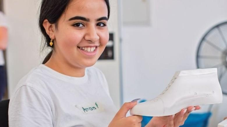 Modebewusst: Schülerin Amani baut einen Sneaker, der am Ende mit  bunten Steinen verziert wird. Foto: Marcus Lorenczat