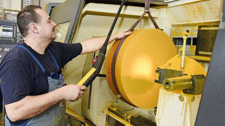 Produktion: Benedikt Dzuck spannt eine Gesadur-Rolle in die Drehmaschine ein.