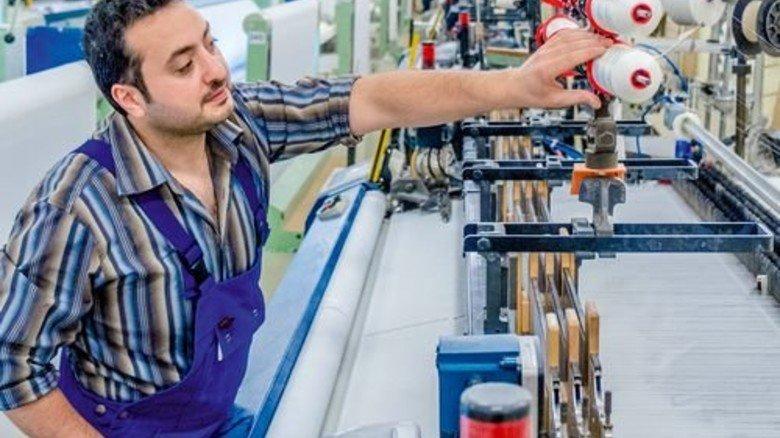 Am Webstuhl: Textilmeister Abdelgani Kortak überprüft eine der Luftdüsenwebmaschinen. Foto: Roth