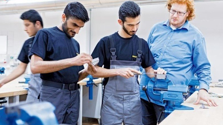 An der Werkbank: Ausbilder Marco Scheler von Kaeser mit Syrer Wasim Osso und Abu Sufyan Warraich aus Pakistan (von rechts). Foto: Werk