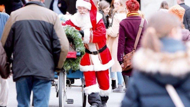 Hat derzeit gut zu tun: Der Weihnachtsmann, vom Fotografen erwischt auf dem Marienplatz in München. Foto: dpa