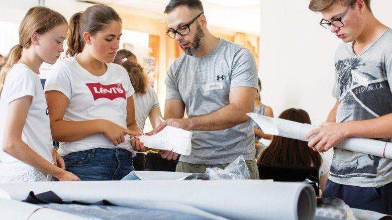 Support vom Profi: Schuh-Designer Jonas Ell (Mitte) hilft den Jugendlichen beim Entwerfen der eigenen Modelle. Foto: Marcus Lorenczat
