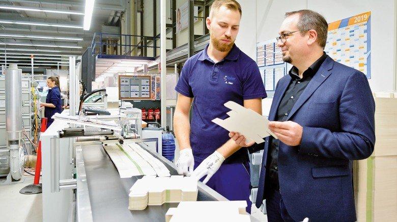 An der Fertigungslinie: Maschinenführer Alexander Herr (links) und Entwicklungsleiter Armin Rambach mit Faltschachteln für Arznei.