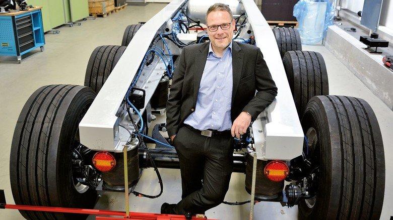 Viele Ideen: Ingenieur Thomas Piroth vor einem Trailermodell mit Luftfederungsachse.