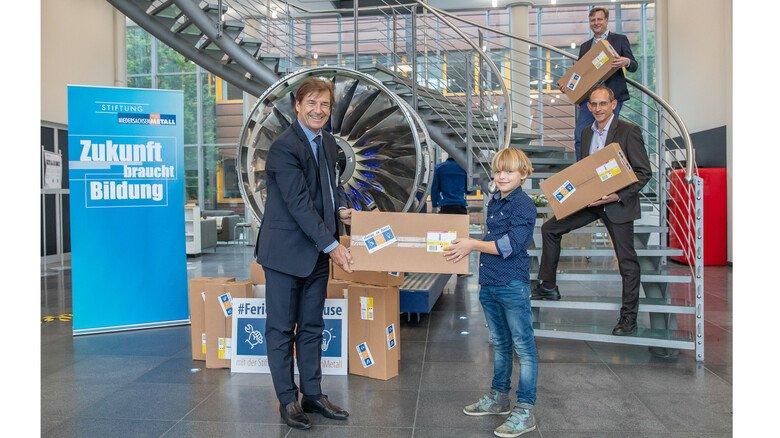 Ein Paket für die Ferien: Hauptgeschäftsführer Volker Schmidt überreicht Henri die Bastelsets.