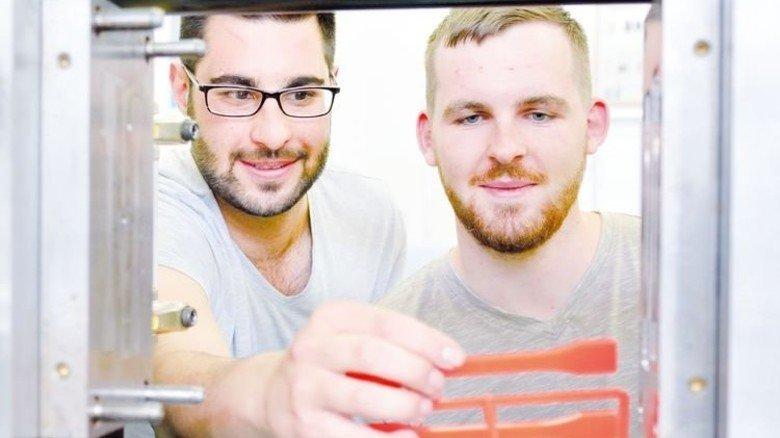 An der computergesteuerten Spritzgießmaschine: Fatih Gümüstepe (links) und Kai Pecher. Foto: Scheffler