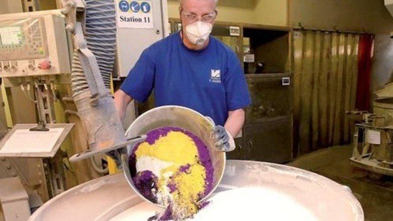 Ein Eimer Farbe: Mitarbeiter Franz Hauber mischt dem Rohstoff Pigmente bei. Foto: Sandro