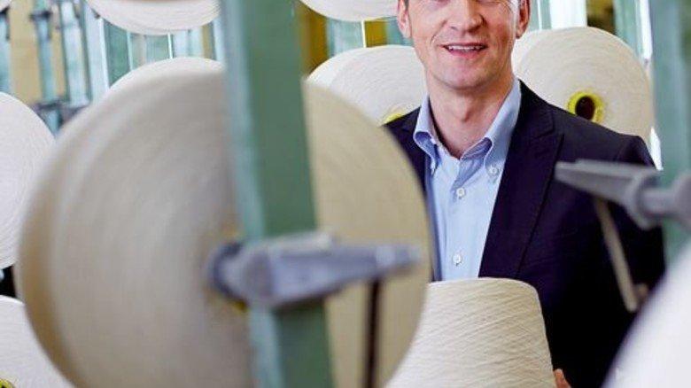 Zwischen Zettelgattern: Geschäftsführer Ernst Grimmelt mit Baumwollgarn aus der eigenen Spinnerei. Foto: Werk