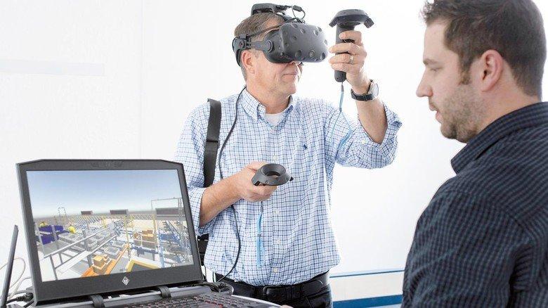 Virtuelle Welt: Dennis Heuser (rechts) zeigt einem Kunden, wie er mittels VR-Brille und Handgeräten die Abläufe in einem Lager steuern kann.