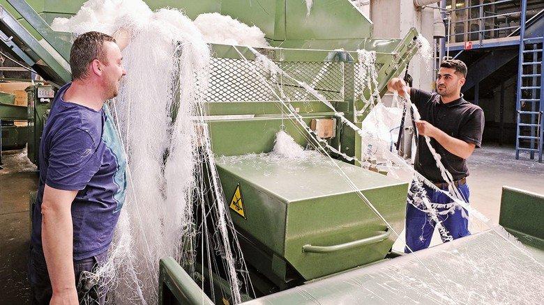 Das waren mal Lkw-Planen: Kevin Cirik und Robert Wojkowiak (links) an einer Zerkleinerungsmaschine.