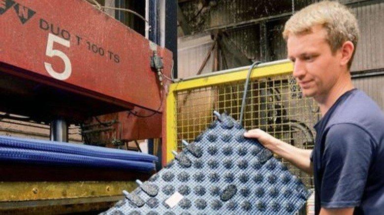 Frisch gepresst: Erik Komnick fertigt kleinere Matten. Die Stifte am Rand dienen zum Verlegen. Foto: Sturm