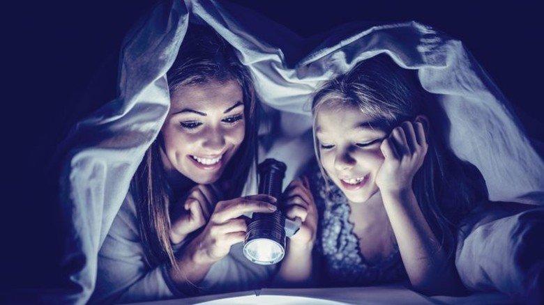 Unter der Bettdecke lesen: Zählt zu den glücklichsten Kindheitserinnerungen. Foto: Fotolia
