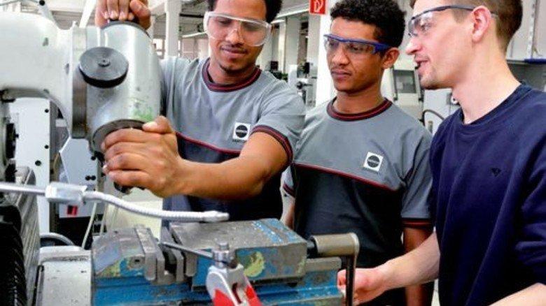 Einstieg: Ausbilder Gaston Weber erklärt Michaele Hayelom und Filimon Solomon (von rechts) den Werkzeugwechsel an einer Fräsmaschine. Foto: Scheffler