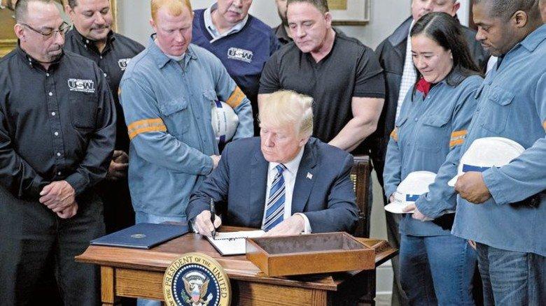 Neulich im Weißen Haus: Stahlarbeiter sehen zu, wie Donald Trump das Zoll-Dekret unterzeichnet. Foto: Getty