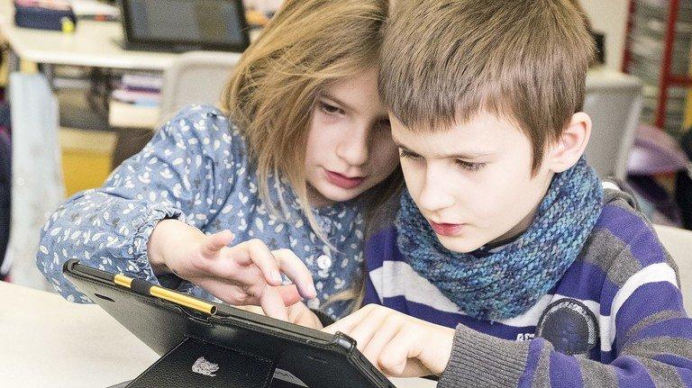 Seltenheit: Junge Schüler mit Tablet-Rechner.