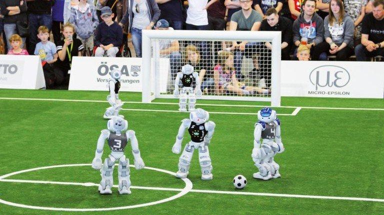 """Erfolgreiche Kicker: Die kleinen Roboter vom Team """"B-Human"""" beim Kampf um den dritten Platz gegen die """"Hulks"""" von der TU Hamburg-Harburg. Foto: Alexis Tsogias"""