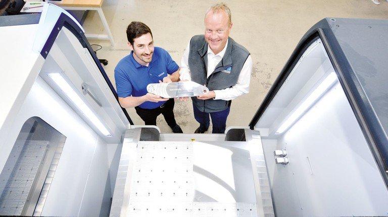Am Vorzeige-Modell MX-Cube: Datron-Geschäftsführer Arne Brüsch (rechts) und Technologe René Rupp zeigen ein in Rekordzeit bearbeitetes Aluminum-Bauteil.