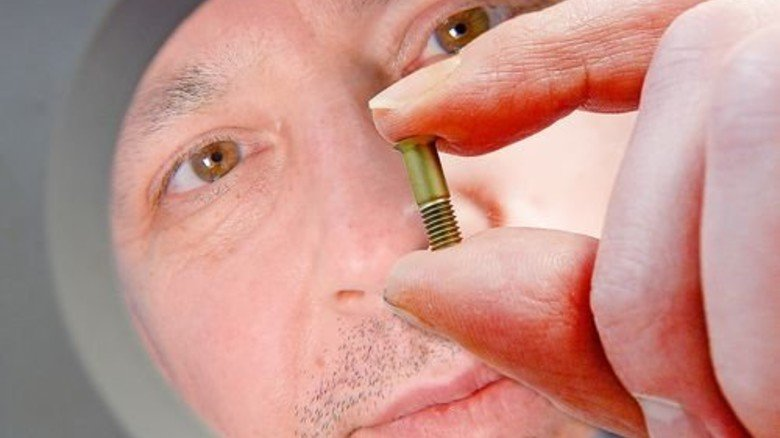 Qualitätsfachmann Thomas Hauser: Mit der Lupe prüft er das Aussehen der Schrauben. Foto: Bahlo